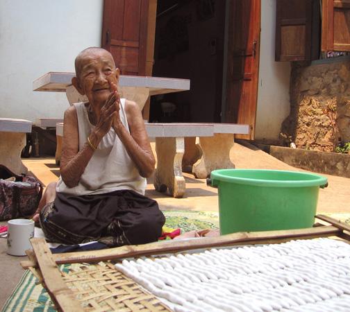 Elderly woman giving the Wai greeting, Mekong River area, Laos