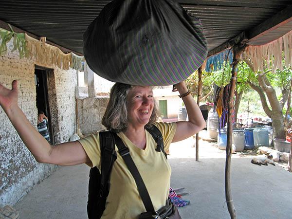 Akaisha trying to balance a bundle on her head, Panajachel, Guatemala