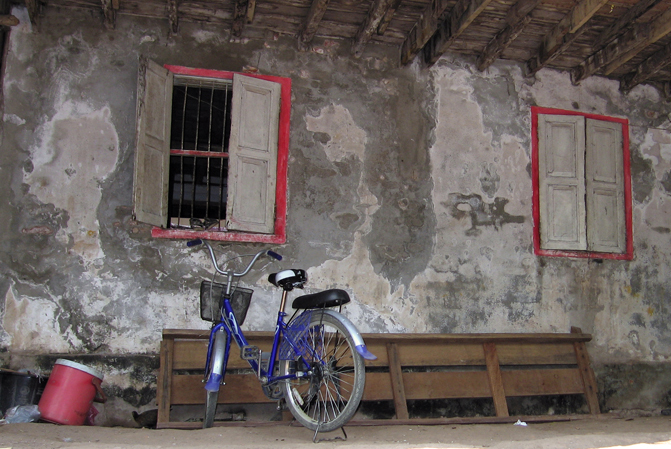 bicycle in front of aging wall, with windows
