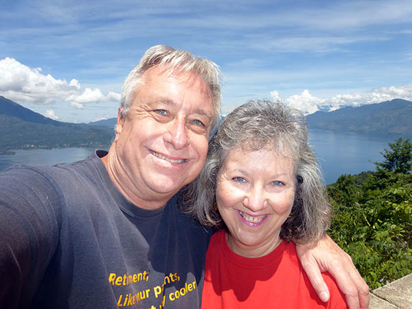 Billy and Akaisha with a panoramic view of Lake Atitlan, Guatemala behind them