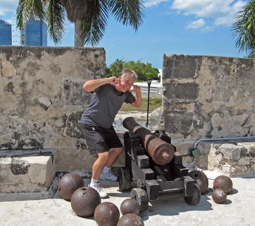 Old rusty cannons and cannon balls of differing sizes