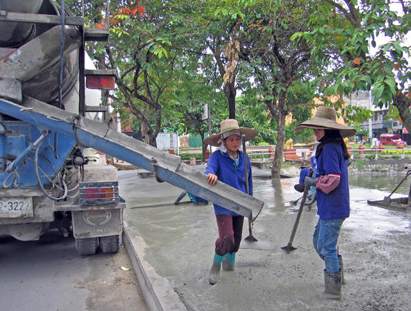 Taking a short break, the girls chat, waiting for the cement truck to give another load. Chiang Mai, Thailand