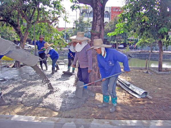 Women construction workers smooth out the cement for making flat sidewalks. Chiang Mai, Thailand