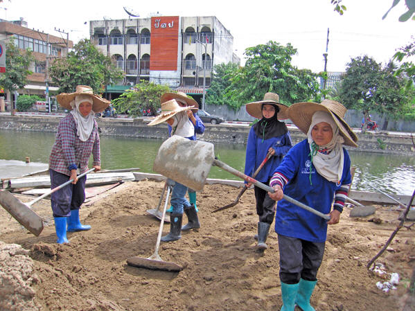 Thai women construction workers, covered head-to-toe flatten the earth. Chiang Mai, Thailand
