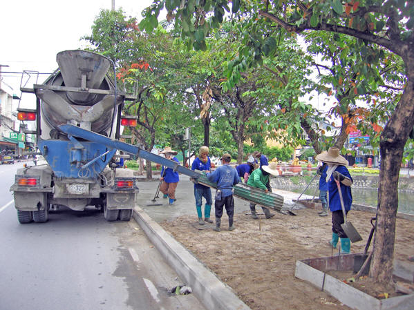 Men and women work together to make these new sidewalks. Chiang Mai, Thailand