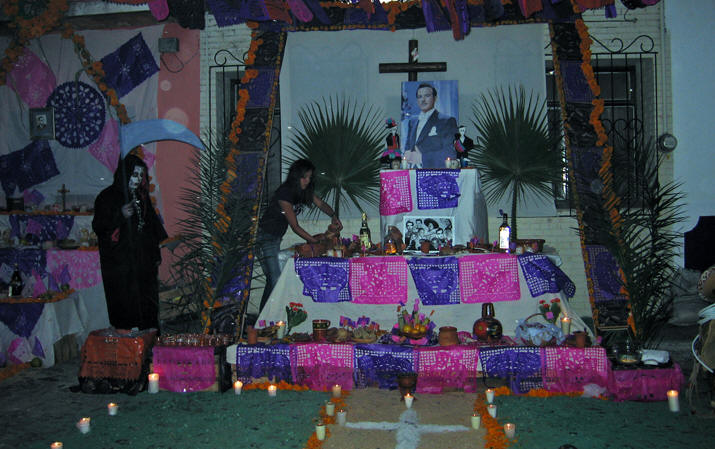 A young woman arranges food on this altar as a skeleton looks on. Days of the Dead, Chapala, Mexico