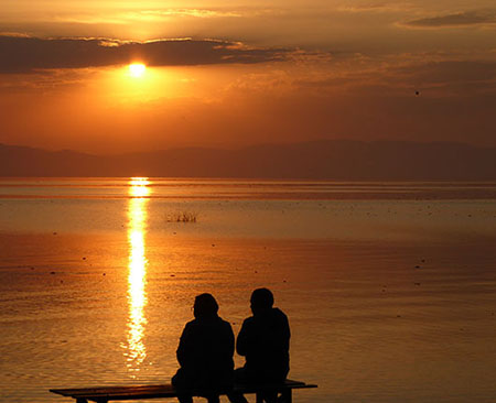 Man and woman sitting on the edge of Lake Chapala in Mexico watching the sunset